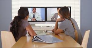 Dos empresarias multi-étnicas que hablan con la tableta en el escritorio Imagen de archivo