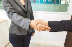 Dos empresarias que sacuden las manos en oficina Imagen de archivo