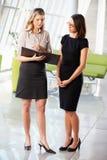 Dos empresarias que tienen reunión informal en oficina moderna Fotografía de archivo