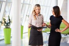 Dos empresarias que tienen reunión informal en oficina moderna Imagen de archivo