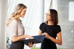 Dos empresarias que tienen reunión informal en oficina moderna Foto de archivo libre de regalías