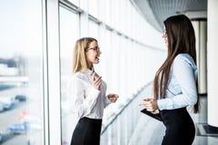 Dos empresarias que tienen reunión informal en oficina moderna Fotografía de archivo libre de regalías