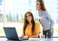 Dos empresarias que tienen reunión informal en oficina Foto de archivo libre de regalías