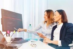 Dos empresarias que trabajan con el ordenador en oficina foto de archivo libre de regalías