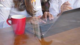 Dos empresarias que trabajan con el ordenador portátil, primer de las manos almacen de video