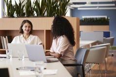 Dos empresarias que trabajan en los ordenadores portátiles que se sientan en la tabla en oficina abierta moderna del plan foto de archivo