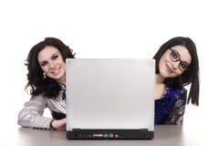 Dos empresarias sonrientes con la computadora portátil fotos de archivo libres de regalías