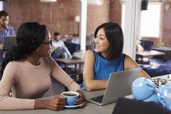 Dos empresarias tienen reunión informal en barra de café de la oficina foto de archivo