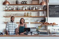 Dos empresarios africanos jovenes sonrientes que se colocan en su contador de la panadería Foto de archivo