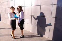 Dos empresarios atractivos de las mujeres jovenes, estudiantes discuten, examen imagenes de archivo