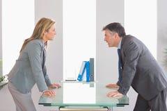 Dos empresarios enojados que discuten en cada lado de un escritorio Imagen de archivo