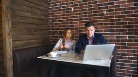 Dos empresarios jovenes que trabajan en el ordenador portátil en cafetería almacen de video