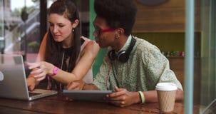 Dos empresarios jovenes que trabajan en el ordenador portátil en cafetería almacen de metraje de vídeo
