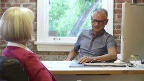 Dos empresarios mayores que tienen reunión en estudio del diseño almacen de metraje de vídeo