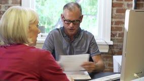 Dos empresarios mayores que tienen reunión en estudio del diseño metrajes