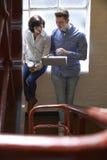 Dos empresarios que tienen reunión informal sobre las escaleras de la oficina Fotografía de archivo libre de regalías