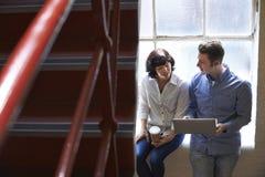 Dos empresarios que tienen reunión informal sobre las escaleras de la oficina imagen de archivo libre de regalías