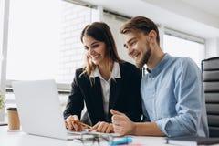 Dos empresarios sonrientes que se sientan junto en una tabla en una oficina moderna que habla y que usa un ordenador portátil fotos de archivo libres de regalías