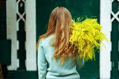 Dos en gros plan de femme avec le bouquet de l'humeur et du week-end jaunes de vacances de ressort de mimosa photos stock