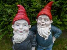 Dos enanos del jardín con los sombreros rojos Imagenes de archivo