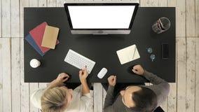 Dos encargados que trabajan discutiendo proyecto sobre la pantalla del ordenador Visualización blanca almacen de metraje de vídeo