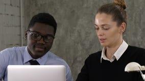 Dos encargados que trabajan en el ordenador portátil almacen de metraje de vídeo