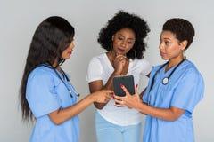 Dos enfermeras con el paciente Fotos de archivo