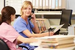 Dos enfermeras que trabajan en la estación de las enfermeras Imágenes de archivo libres de regalías