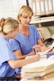 Dos enfermeras que trabajan en la estación de las enfermeras Foto de archivo