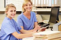 Dos enfermeras que trabajan en la estación de las enfermeras Foto de archivo libre de regalías