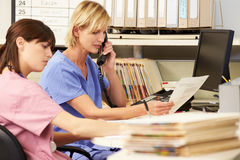 Dos enfermeras que trabajan en la estación de las enfermeras Fotos de archivo libres de regalías