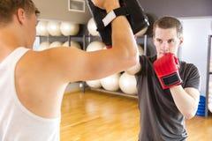 Dos enfocaron a los hombres que entrenaban al boxeo en el gimnasio de la aptitud Foto de archivo libre de regalías