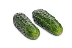 Dos enteros, jugosos, difícilmente y pepinos verdes claros curruscantes, en un fondo blanco Verduras y vitaminas sanas Fotos de archivo libres de regalías