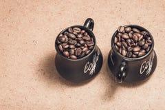 Dos entonaron las tazas con los granos de café en la madera Fotografía de archivo