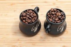 Dos entonaron las tazas con los granos de café en tablón de madera Foto de archivo