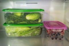 Dos envases de comida plásticos con la verdura verde y uno con las bayas en un estante de un refrigerador Fotografía de archivo