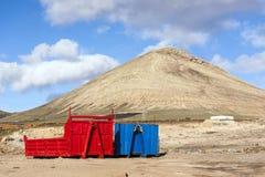 Dos envases en rojo y azul en paisaje volcánico Imagen de archivo libre de regalías