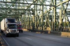 Dos equipamentos caminhões grandes semi da classe diferente e do tamanho que conduzem no imagens de stock
