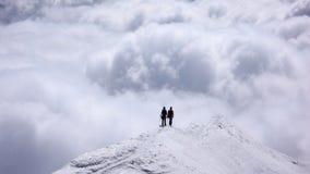 Dos escaladores de montaña femeninos en un canto estrecho de la cumbre alto sobre los bancos de nube en los valles abajo Fotos de archivo