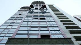 Dos escaladores industriales son el lavarse, limpiando la fachada de un edificio de oficinas moderno metrajes