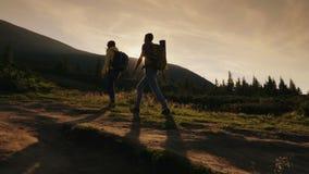 Dos escaladores suben para arriba la montaña en el sol, vista lateral Concepto - triunfos y logros almacen de metraje de vídeo