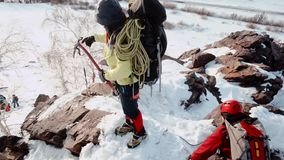 Dos escaladores subieron para arriba en una cuesta grande y escarpada de una monta?a nevosa y tiraron de la cuerda con la cual al metrajes