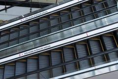 Dos escaleras m?viles en el primero plano con una muestra en espa?ol que dice evitan entrar en la direcci?n opuesta imagenes de archivo