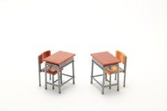 Dos escritorios miniatura de la escuela en el fondo blanco Fotografía de archivo