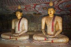 Dos esculturas antiguas del Buda asentado en el templo budista de la cueva (aproximadamente yo siglo A.C.) Foto de archivo libre de regalías