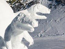 Dos esculturas de Dinosaurus hechas de nieve como decoraci?n en una cuesta del esqu? imagen de archivo libre de regalías
