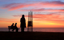 Dos esculturas dos espectadores, escultura de la salida del sol por el mar Foto de archivo