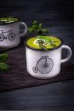 Dos esmaltaron las tazas de sopa poner crema vegetariana con el espárrago verde, la albahaca y las semillas de sésamo negras en f Foto de archivo libre de regalías