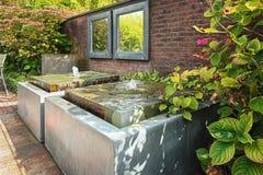 Dos espejos en la pared del jardín con el elemento decorativo del agua dos Foto de archivo libre de regalías