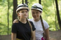 Dos espeleólogos adolescentes de las muchachas en cascos en el bosque en d soleada Foto de archivo